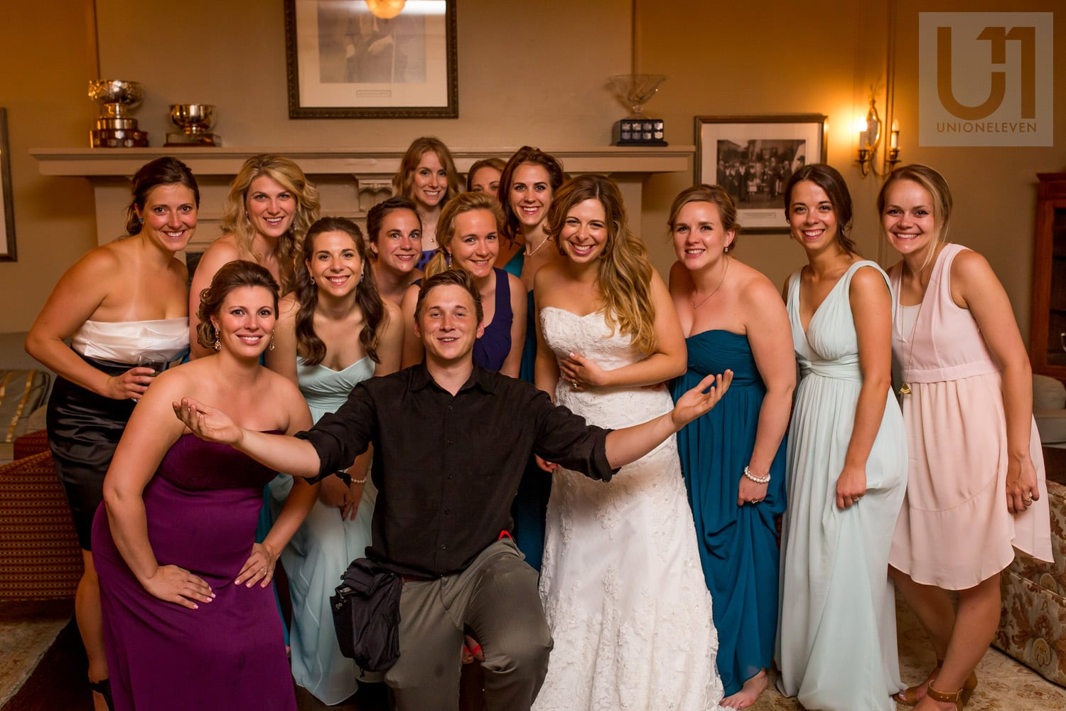 photographer kneeling, surrounded by bride, bridesmaids and female guests at wedding reception in Gatineau