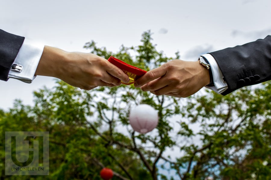 two hands handing off red envelope during traditional chinese tea ceremony in Ottawa