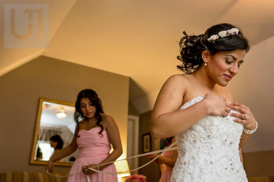 bridesmaid lacing bride's gown