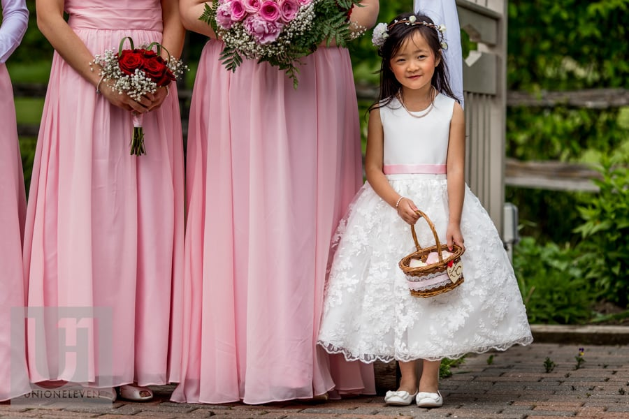 flower girl standing beside bridesmaids in their pink dresses at Strathmere wedding in Ottawa