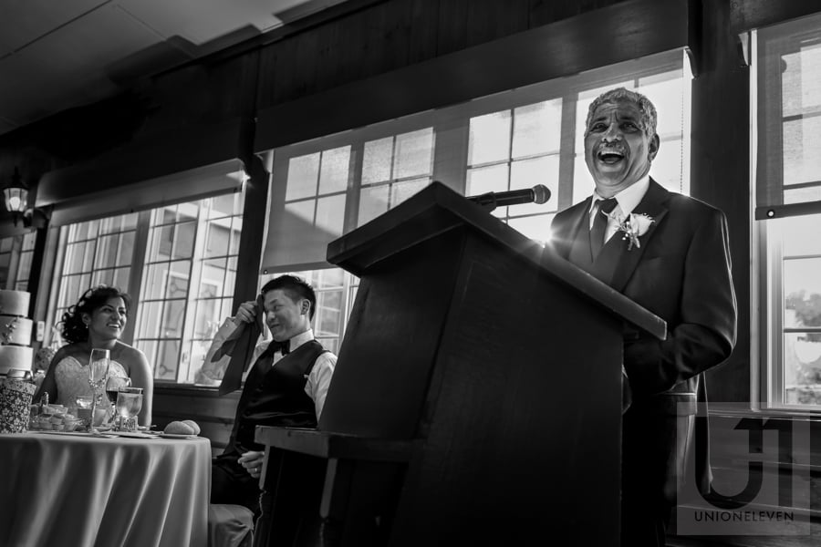 father of the bride making a speech while groom holds napkin up to his forehead, pretending to sweat, during wedding reception