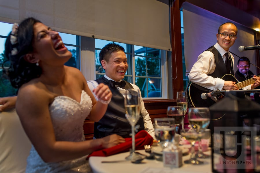 bride and groom laughing while groomsman performs with a guitar