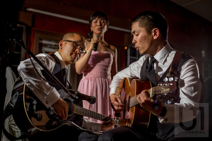 two groomsmen and a bridesmaid playing guitar and  singing during wedding reception at Strathmere