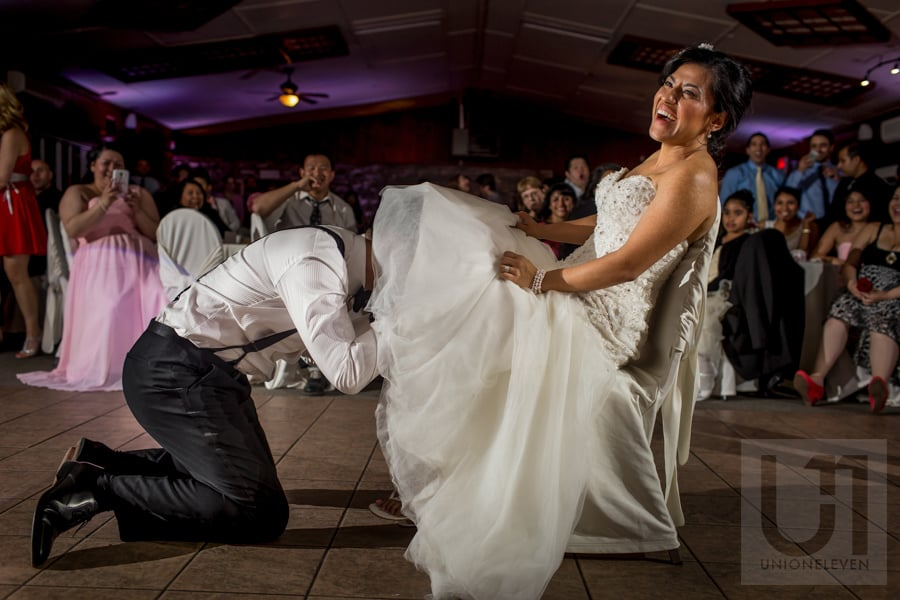 groom digging for bride's garter under the bridal gown while bride laughs
