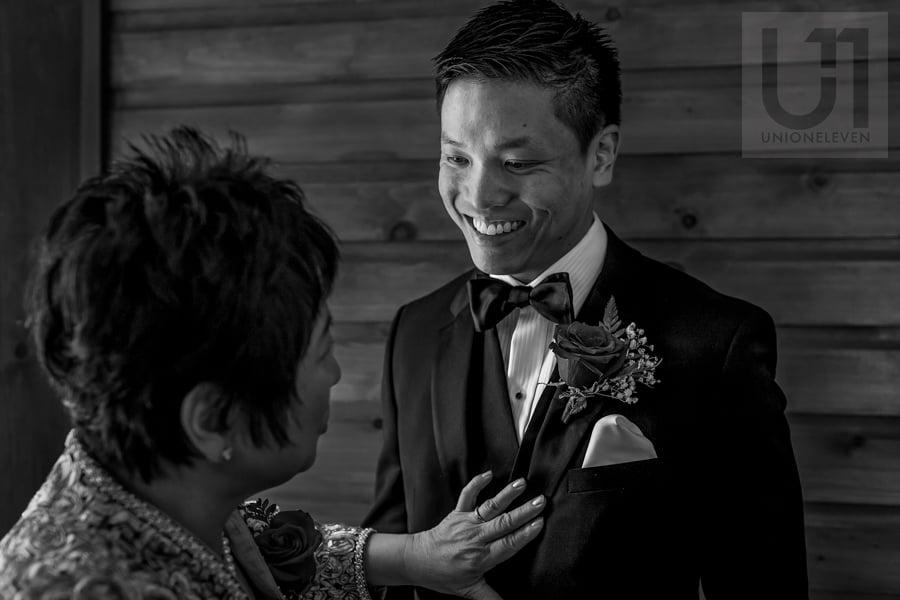 mother of groom adjusting groom's suit