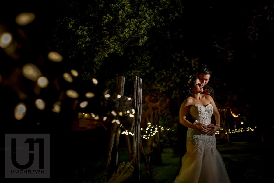 nighttime portrait of bride and groom nuzzled in an embrace next to a string of lights