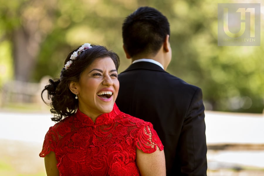 bride in red dress back to back with her groom, waiting to reveal herself during first look
