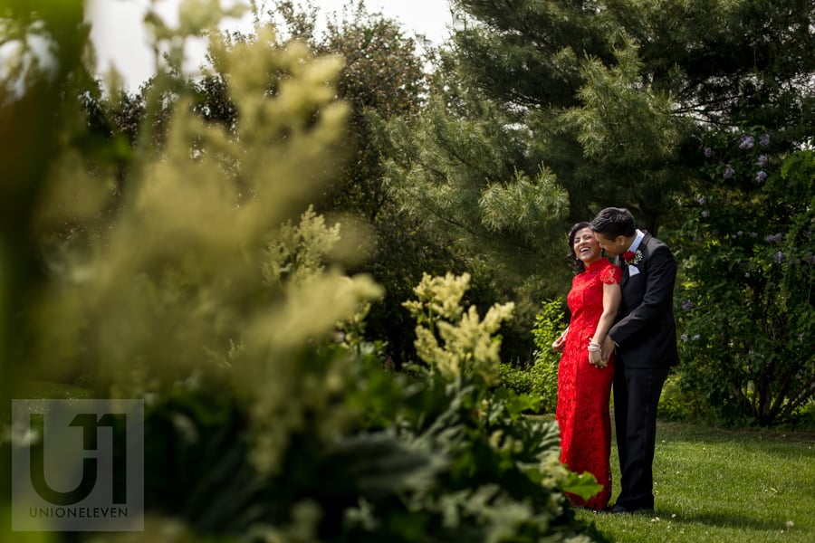 bride in red dress and groom sharing a laugh , surrounded by trees and bushes