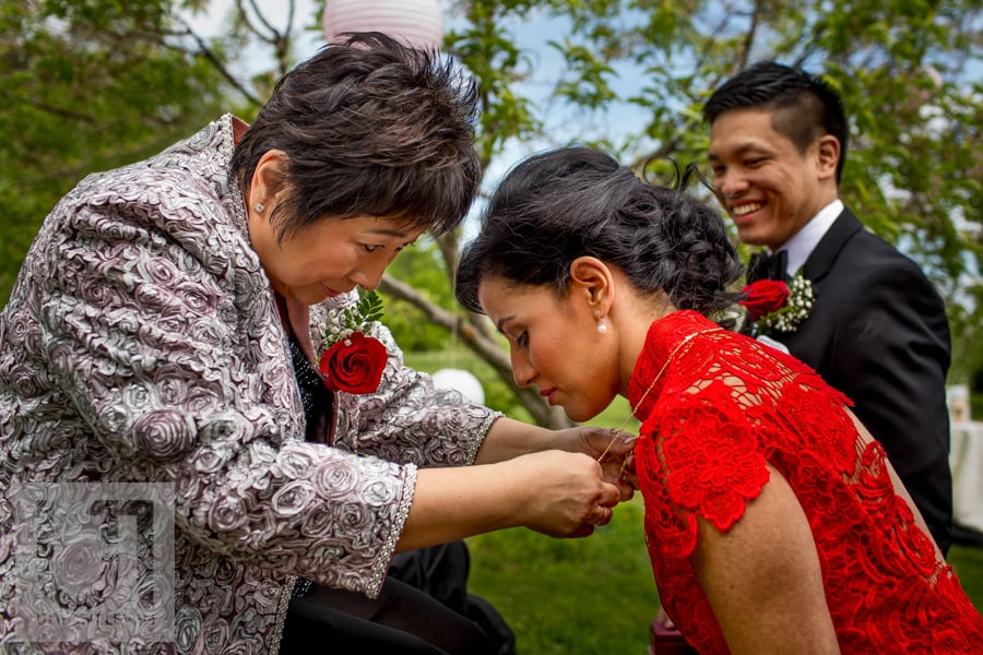 bride in red dress receiving gift from mother of the groom during chinese tea ceremony