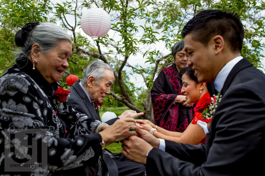 bride and groom exchanging tea cups with grandparents during chinese tea ceremony