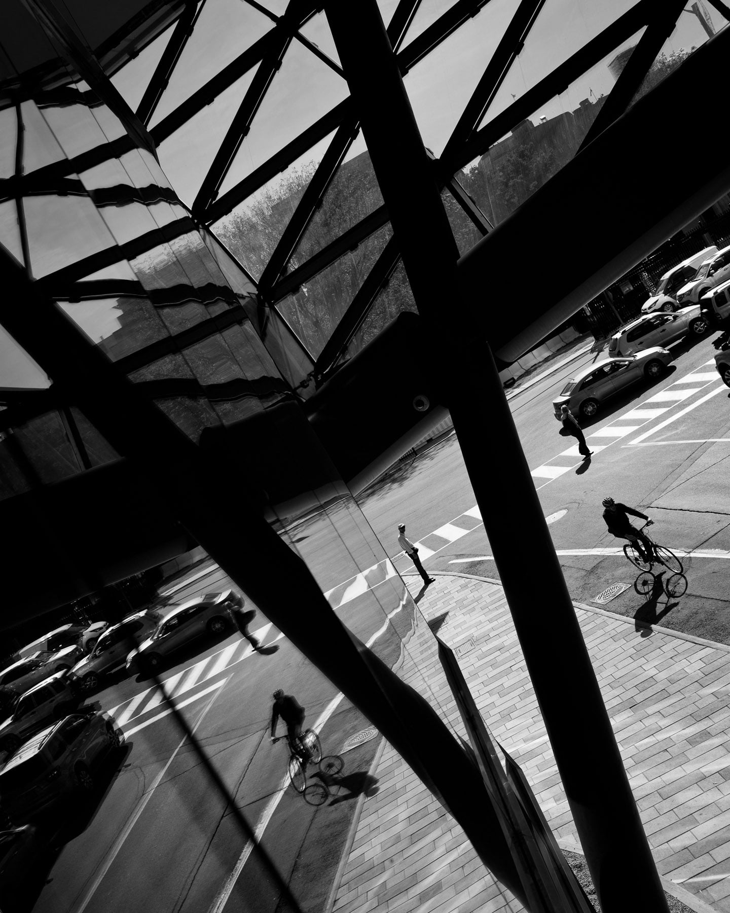 Street photography of an urban setting, showcasing person on a bicycle and their reflection on the side of a building.