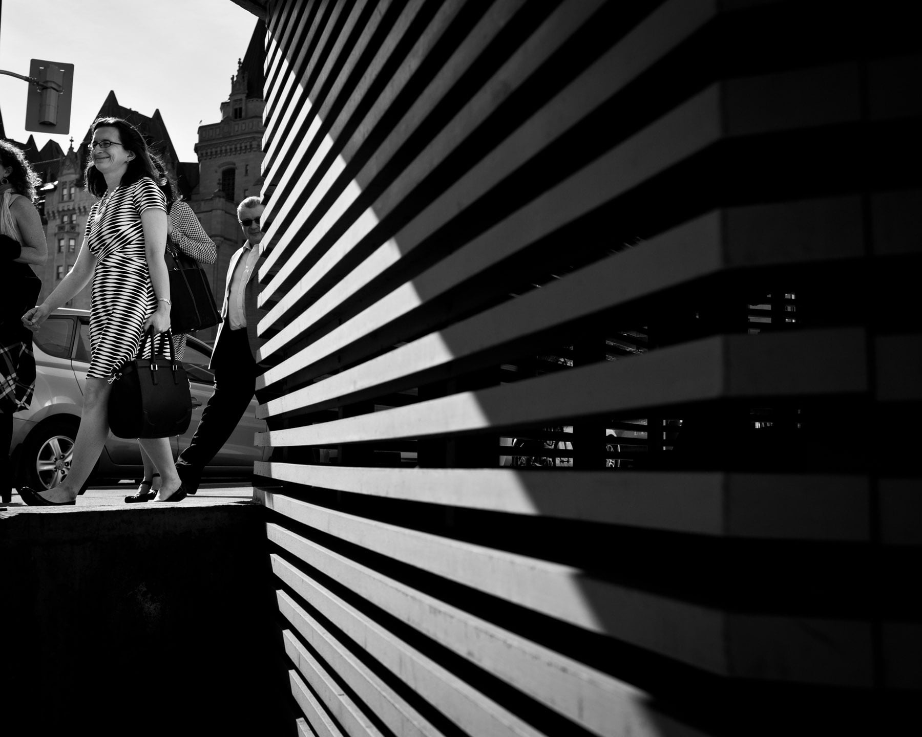 Street photography of a woman in striped dress walking downtown Ottawa, juxtaposition against a striped wall of a building.