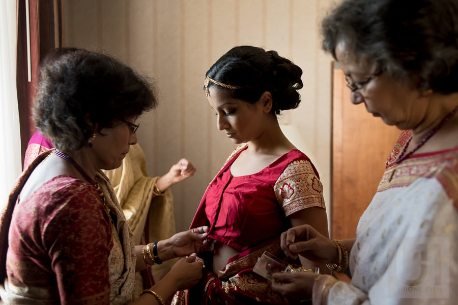 bride in traditional Hindu outfit being dressed by mother and family members