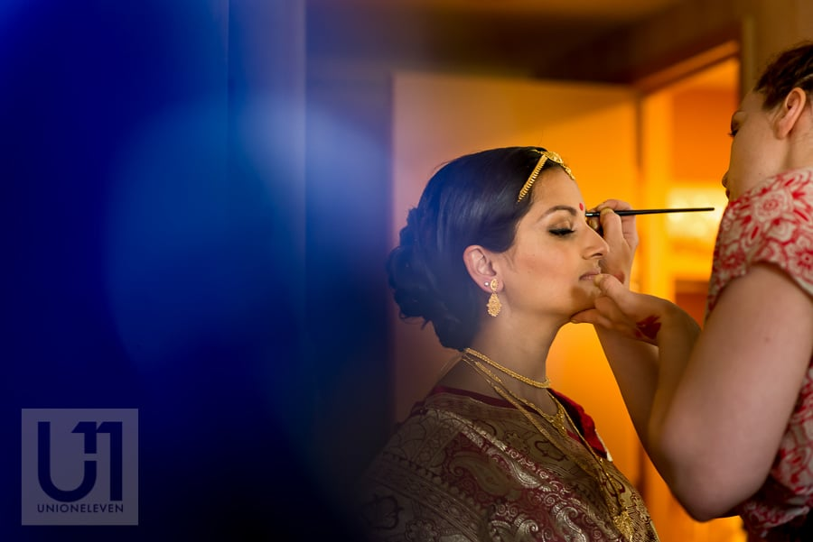 Hindu bride in traditional dress having her make up done