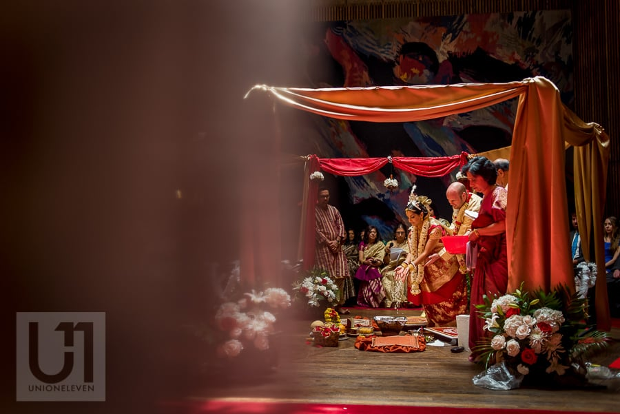 bride pouring rice with groom during traditional Hindu wedding ceremony at the National Arts Centre in Ottawa