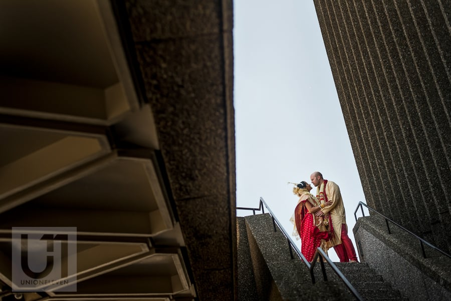 portrait of bride and groom in traditional Hindu dress, on staircase in downtown Ottawa