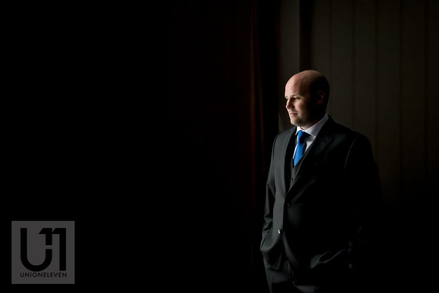 portrait of groom standing in front of a window in his suit