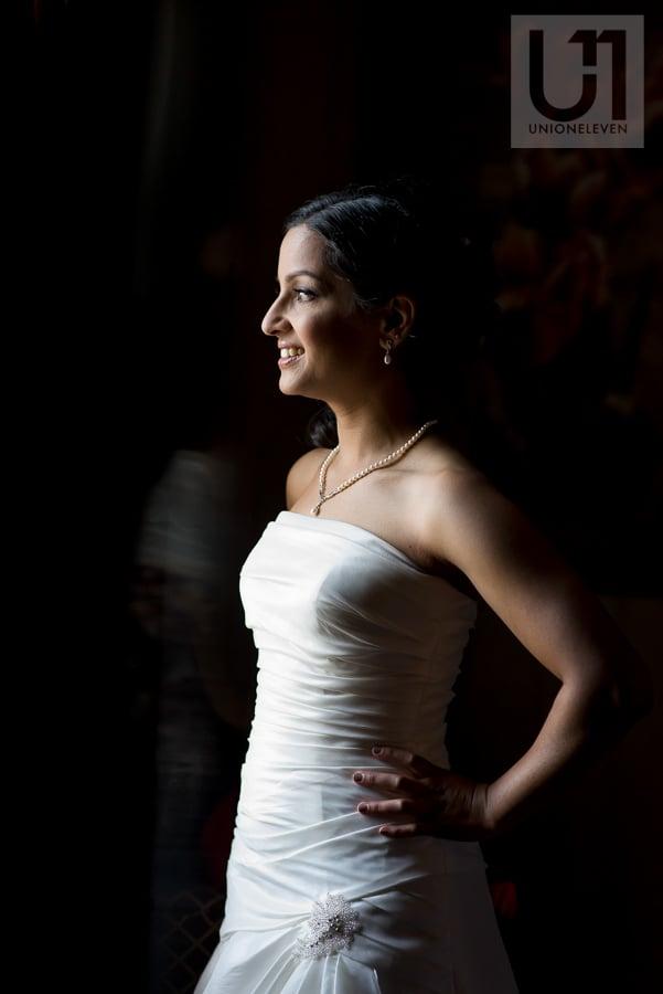 portrait of bride standing in front of window in her wedding gown