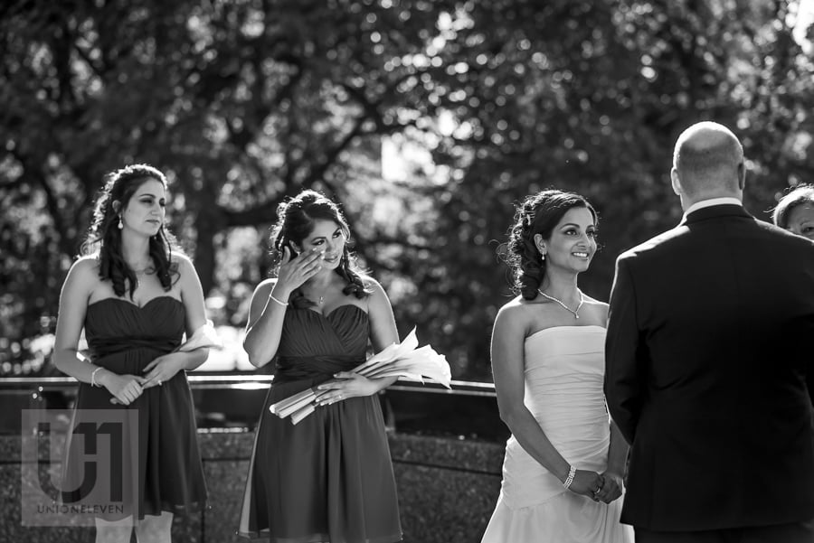 bride looking at groom lovingly during wedding ceremony, while bridesmaid wipes her own tears in the background