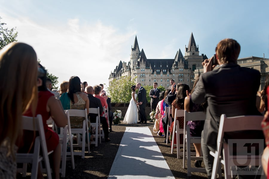 bride and groom sharing first kiss during rooftop wedding ceremony at the National Arts Centre in Ottawa, with the Chateau Laurier in the background