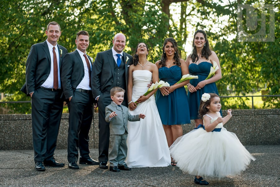 portrait of wedding party where the flower girl is running away and the bride is hysterically laughing