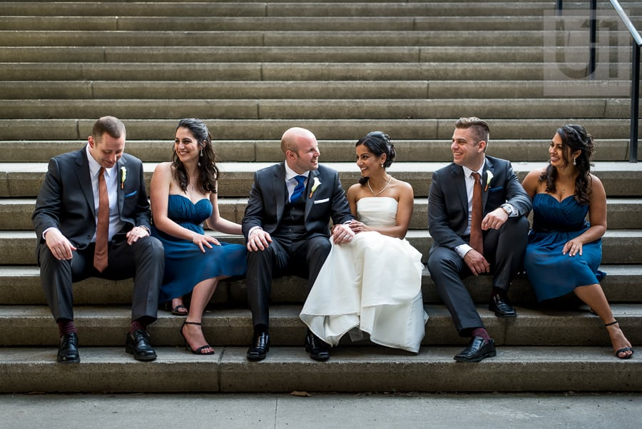 casual portrait of wedding party sitting on steps in downtown Ottawa