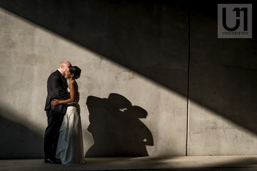 portrait of bride and groom against concrete wall with strong directional light, in downtown Ottawa