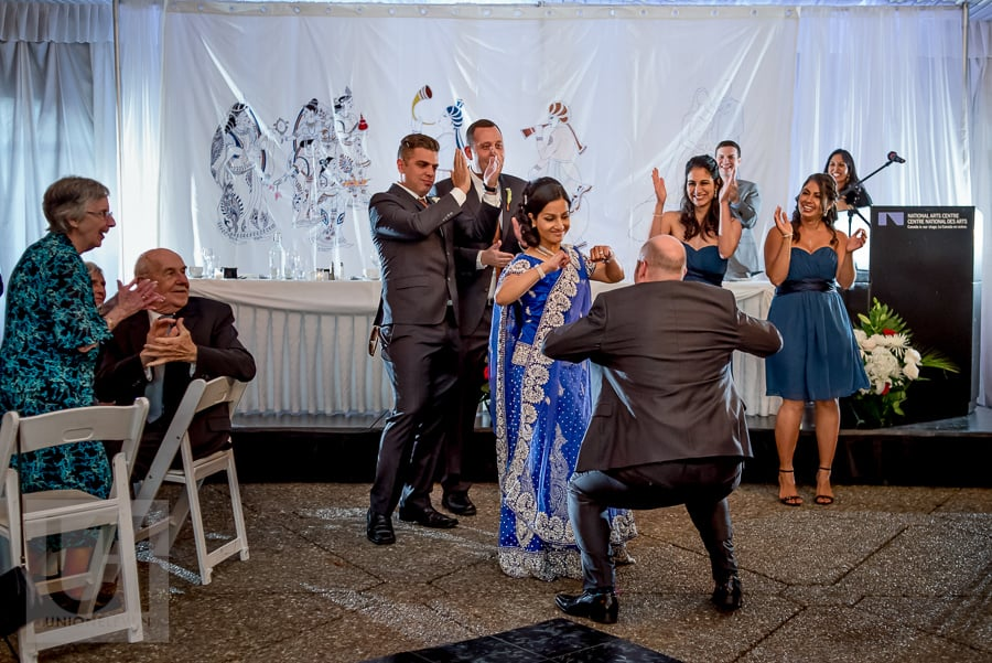 bride in Hindu dress dancing with her groom upon entering rooftop reception at the National Arts Centre in Ottawa