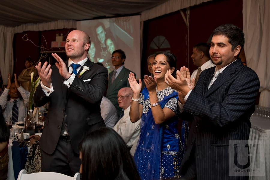 bride and groom standing, clapping during wedding reception at the National Arts Centre in Ottawa