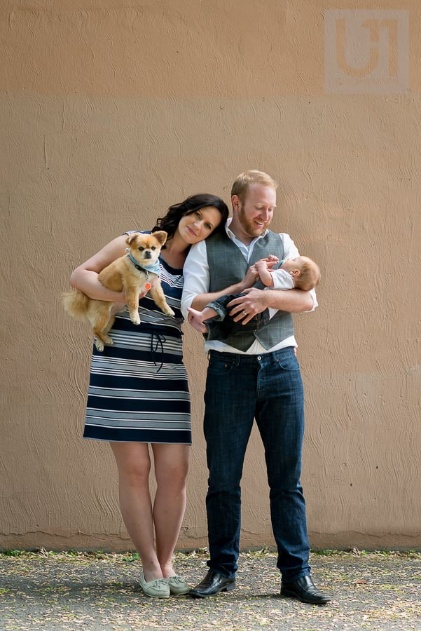 woman holding dog and resting her head on man who is holding their baby boy in front of a beige wall