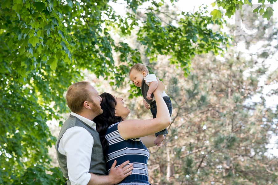 man holding his wife at hips while she holds their baby boy up in the air at Windsor Park, Ottawa