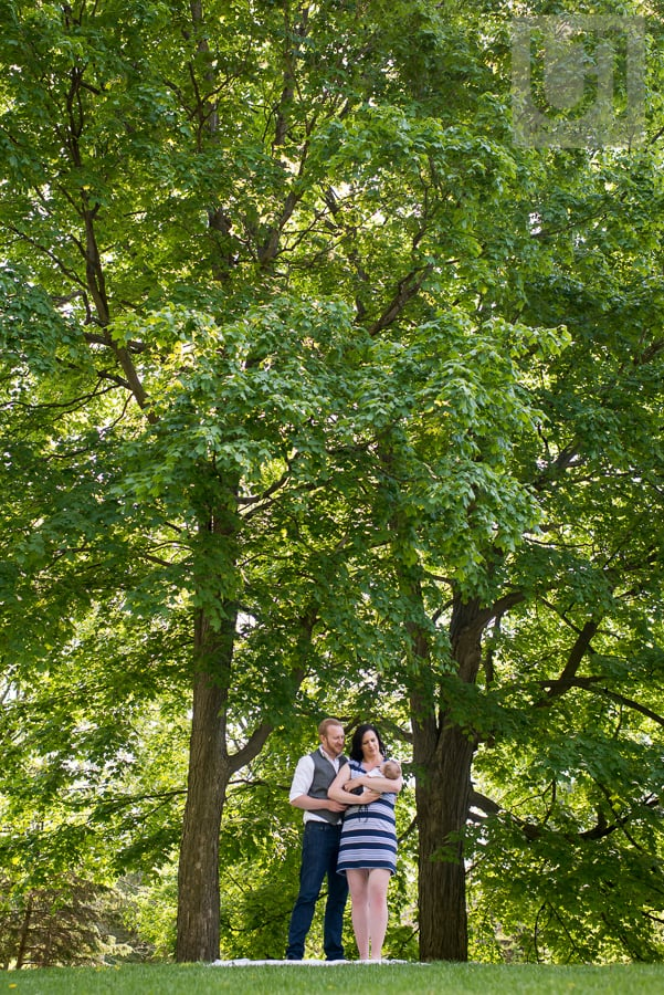 man and woman standing between trees in park while holding their baby boy