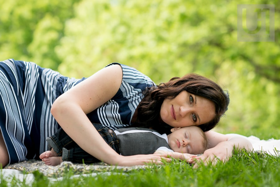 mother resting her face on her baby boy as he lies on a blanket in the middle of Windsor Park in Ottawa
