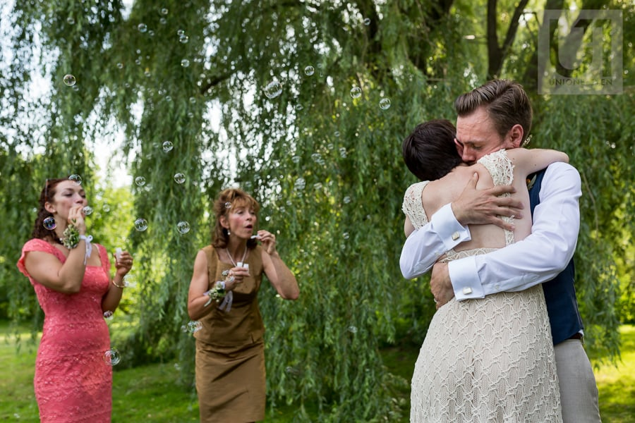 Bride and groom hugging while guests blow bubbles at them at the Arboretum in Ottawa.