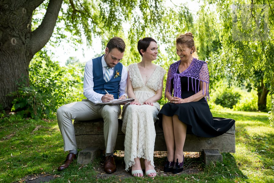Groom signing marriage certificate while he, his bride and the officiant sit on a bench in the Arboretum in Ottawa.