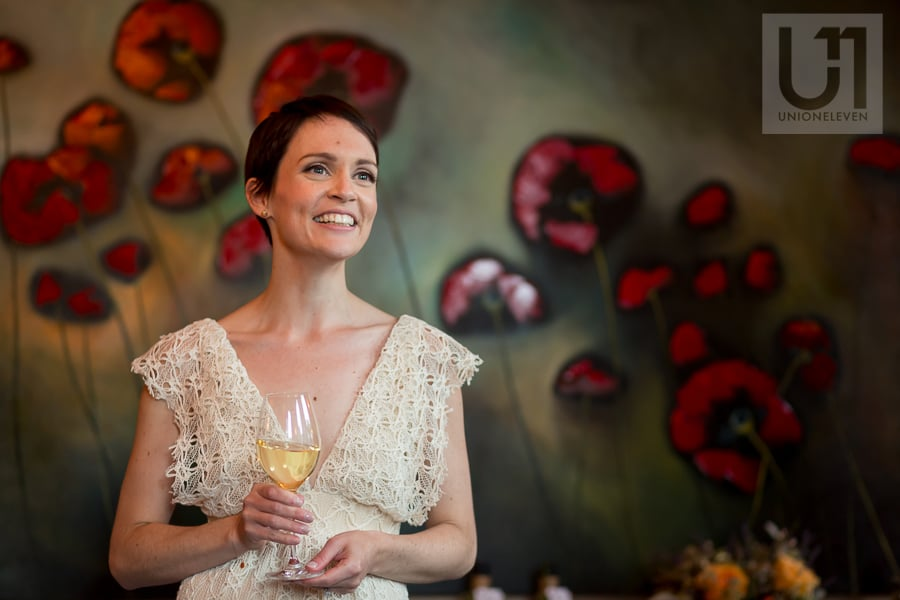 Bride holding glass of white wine in front of large painting of poppies at Beckta in Ottawa.