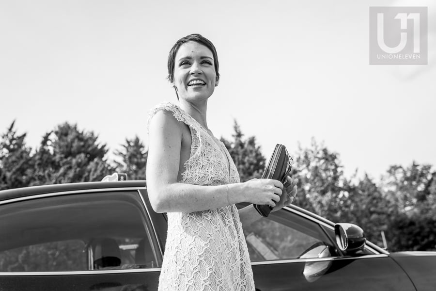 Black and white image of a woman standing outside of car, holding a wallet with a big smile on her face.