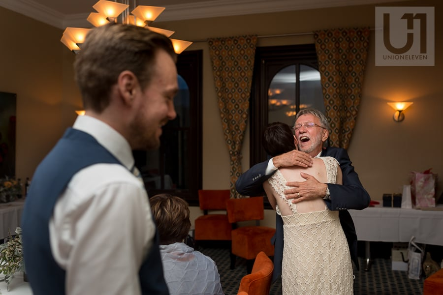Father of bride hugs bride while groom watches on at Beckta in Ottawa.