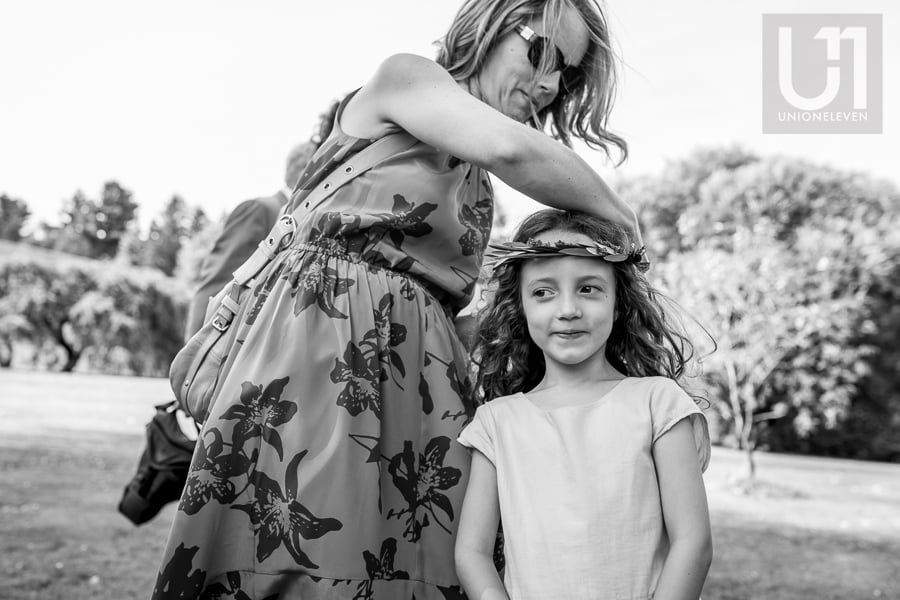 Flower girl having a flower crown adjusted on her head by woman.