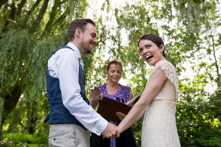 Man and woman standing in front of officiant. holding hands while woman laughs with excitement.