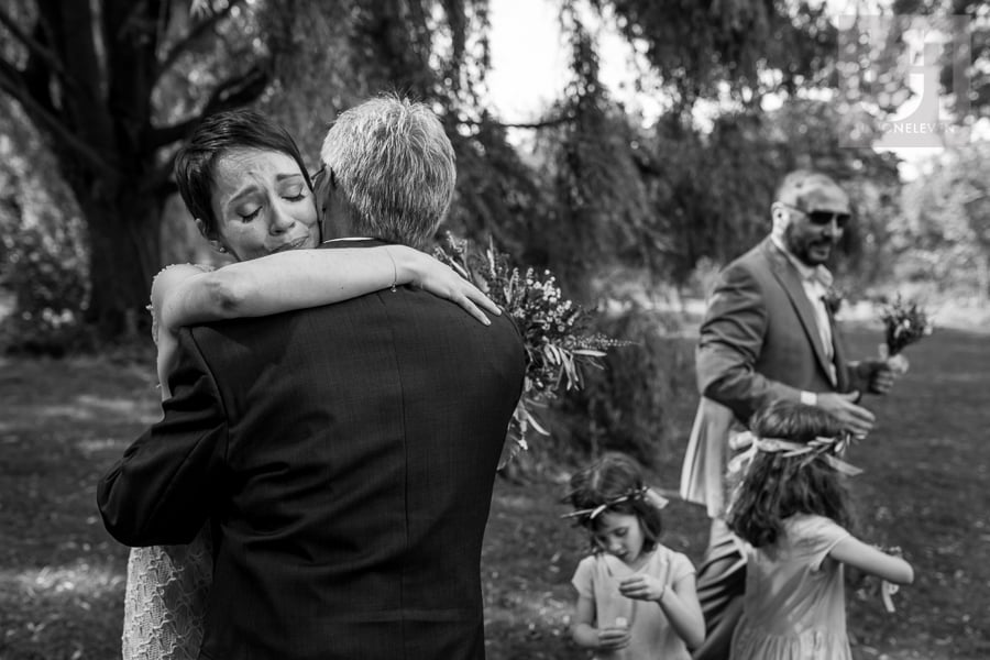 Black and white image of bride hugging man after wedding ceremony, crying.