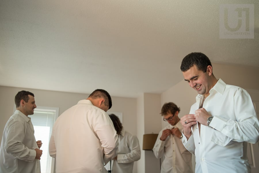 Man buttoning up white shirt in a room with male friends that are also getting dressed