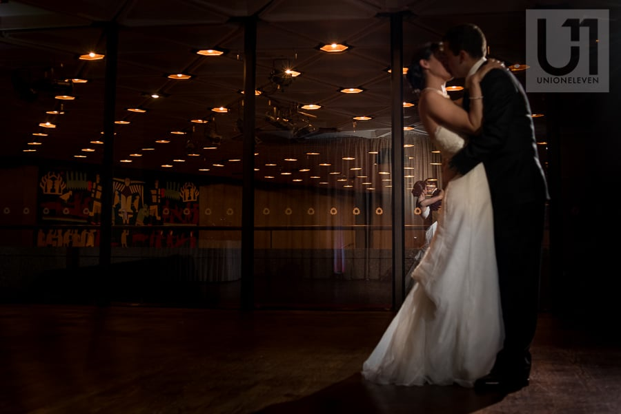 Reflection of bride and groom dancing and kissing in glass wall at the NAC in Ottawa.