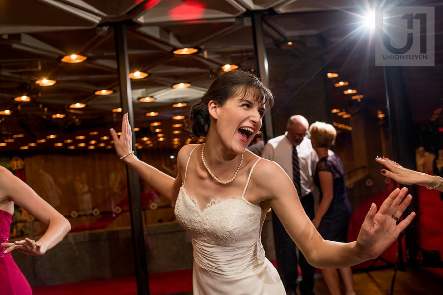 Bride laughing and dancing on dance floor with her arms stretched out to either side of her at NAC in Ottawa.