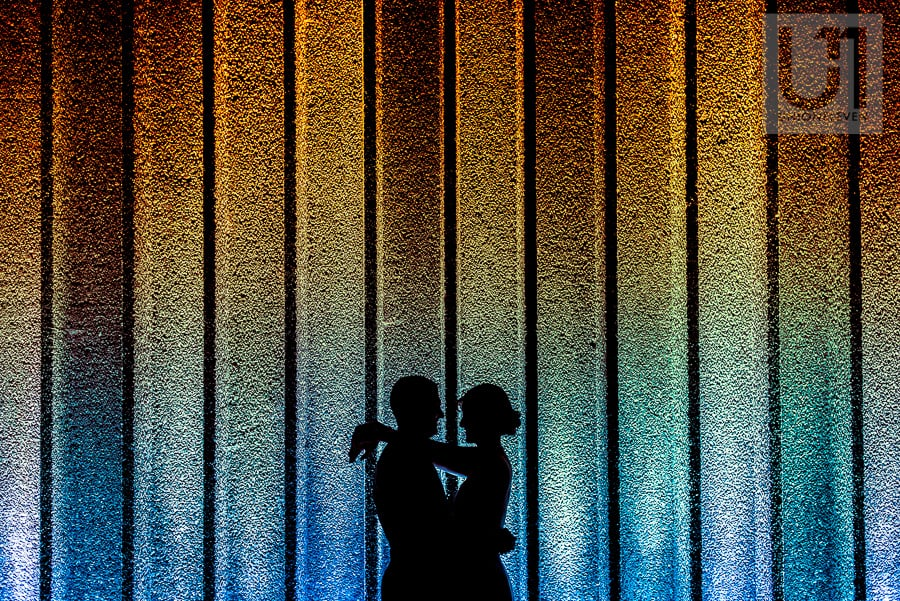 Silhouette of couple embracing each other in front of wall with vertical lines , fading from a warm amber colour up top to a cool blue at the bottom.