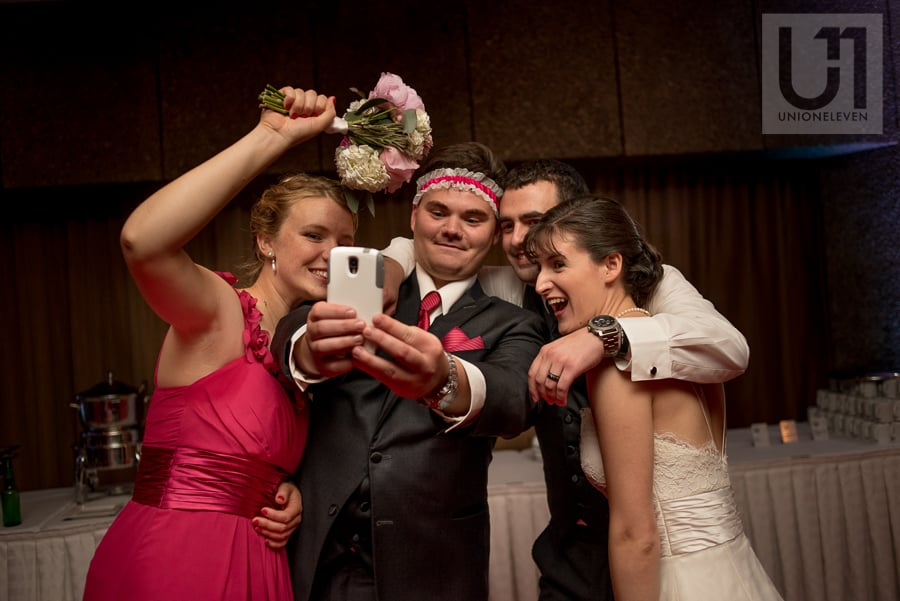 Bride, groom and two friends taking a selfie with a phone at wedding reception in Ottawa.
