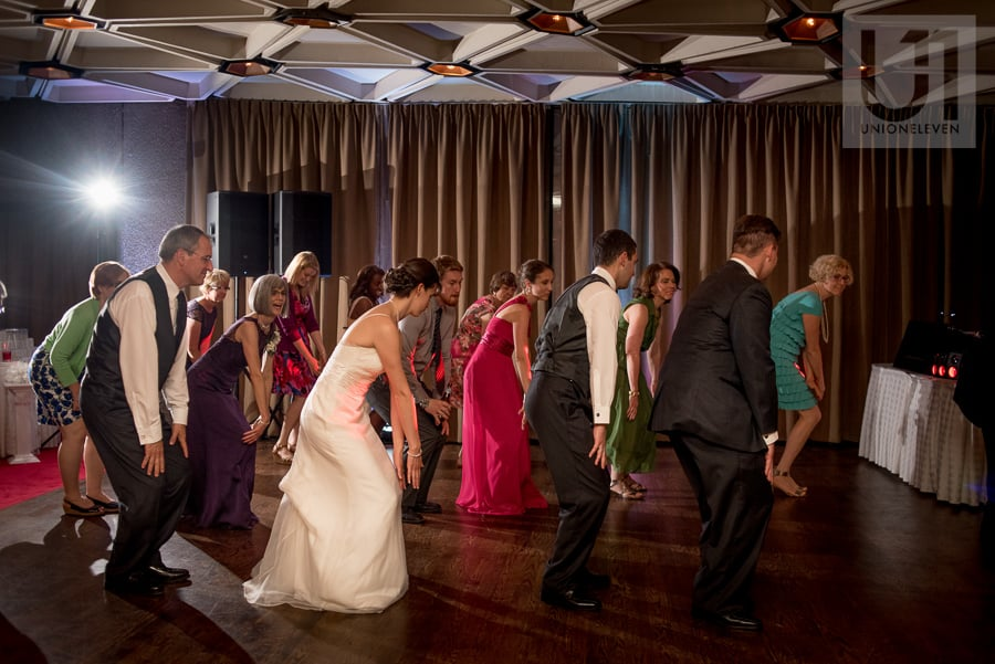 Bride and groom in a line dance with their guests on the dance floor at the National Arts Centre in Ottawa.