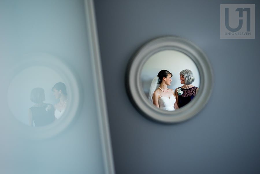 Reflection of a bride and her mother in a small circular mirror on blue wall.