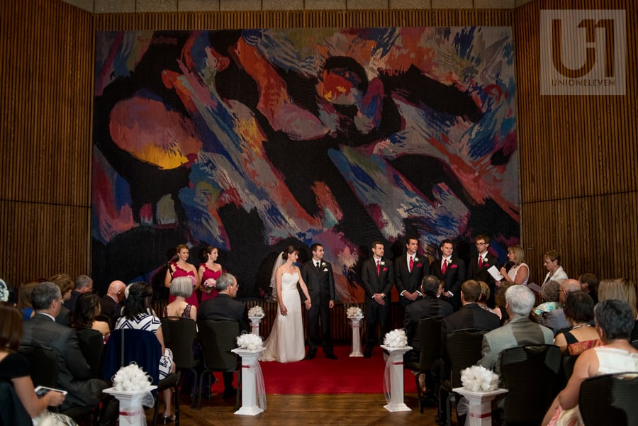 Bride and groom standing in front of their guests alongside their wedding party at NAC in Ottawa