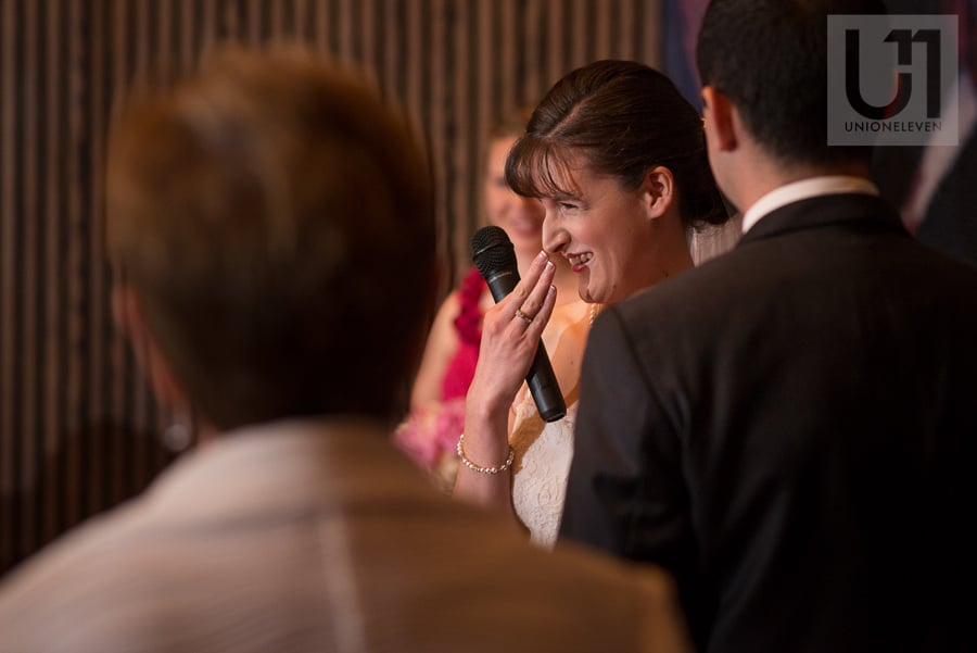 Bride giggling while holding a microphone at NAC in Ottawa